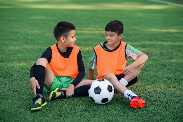 Юные футболисты отдыхают на искусственной траве Premium Фотографии