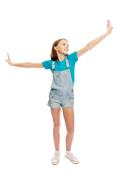 Teen girl in denim overalls in a flying pose, full height. isolated on a white background Premium Photo