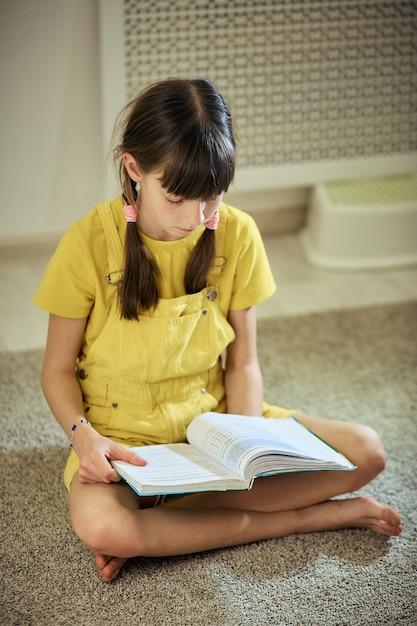Teen girl doing homework sitting on the carpet in her room Premium Photo