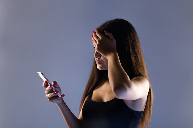Teen girl excessively sitting at the phone at home. he is a victim of online bullying stalker social networks. Premium Photo