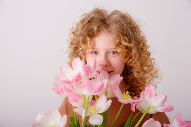 Teen girl holding a bouquet of pink tulips Premium Photo
