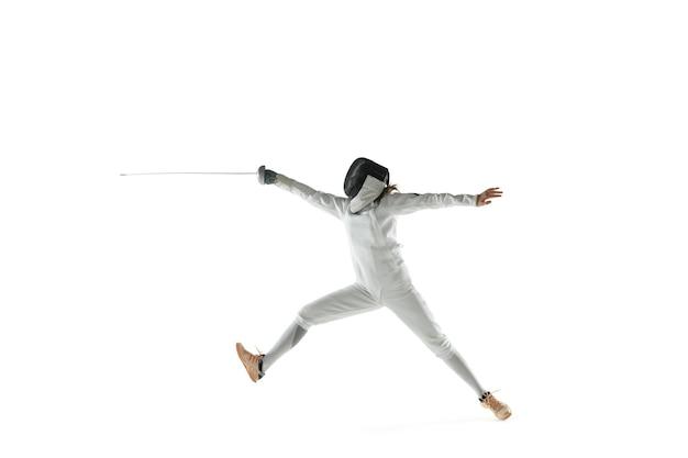 白いスタジオの背景に分離された手に剣とフェンシングの衣装を着た10代の少女。若い女性の白人モデルは、動き、行動の練習とトレーニングをしています。コピースペース。 無料写真