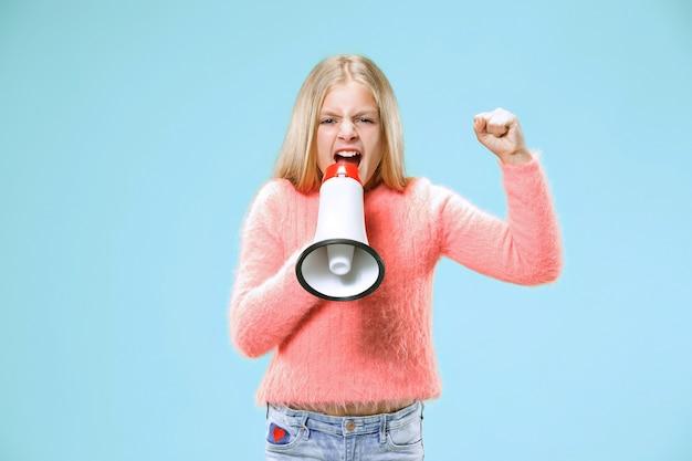 Девушка-подросток делает объявление с мегафоном в голубой студии Бесплатные Фотографии