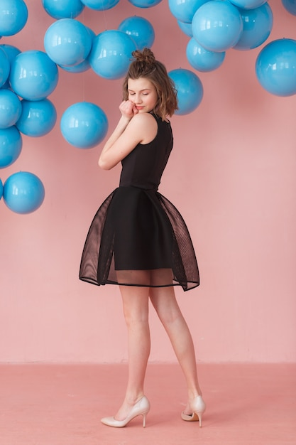 Teen girl posing on pink wall and blue balloons backdrop. Free Photo