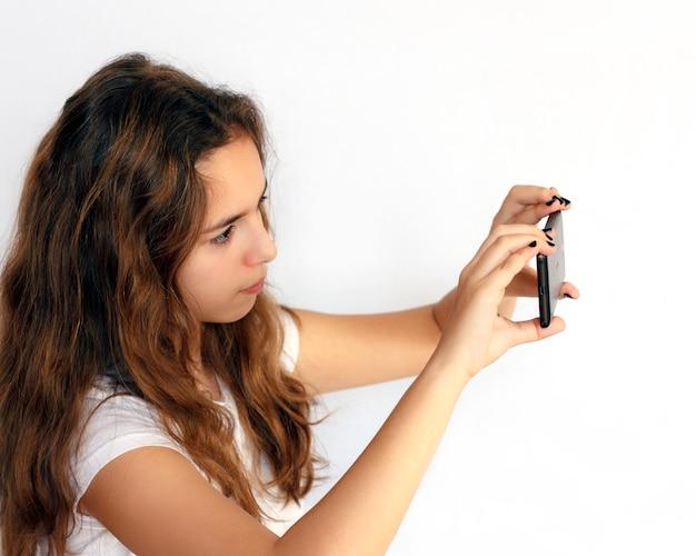 Teen girl shoots video on a black smartphone Premium Photo