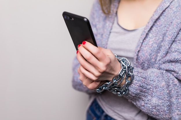Teen girl with chain locked hands using a smartphone isolated Free Photo