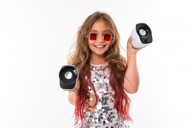 Девочка-подросток с длинными светлыми волосами, окрашенными в розовые кончики, в блестящем светлом платье, черно-белых кроссовках, очках, стоит в наушниках, держит в руках музыкальные колонки Premium Фотографии