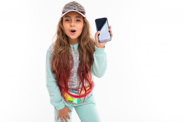 Teen girl with long blonde hair dyed with tips pink, in shiny white cap, light blue sports suit, belt bag smiles and shows the phone Premium Photo