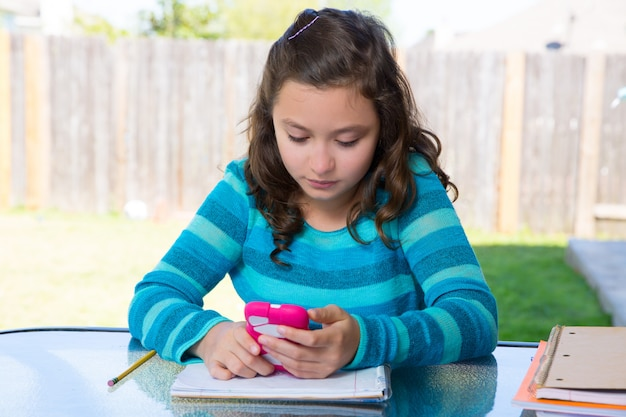 Teen girl with smartphone doing homework Premium Photo