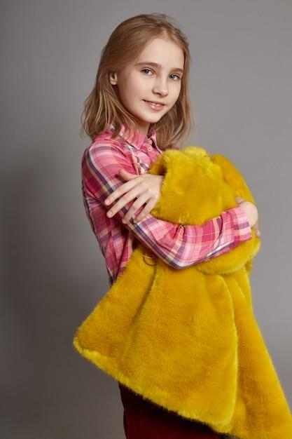 Teen girl in yellow faux fur coat, portrait Premium Photo