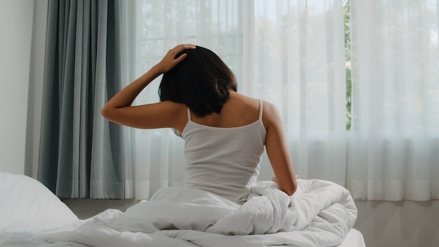 Teen hispanic woman wakes up at home. young asian girl stretching after awake sleep all night starting a new day with energy and vitality felt very refreshed on bed near window in bedroom at morning. Free Photo