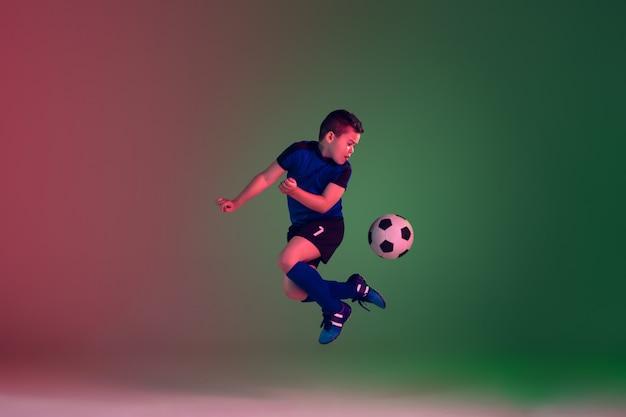 Подросток мужской футбол или футболист, мальчик на градиентный фон в неоновом свете - движение, действие, концепция деятельности Бесплатные Фотографии
