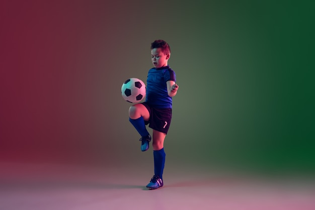 Teen male football or soccer player, boy on gradient background in neon light - motion, action, activity concept Free Photo