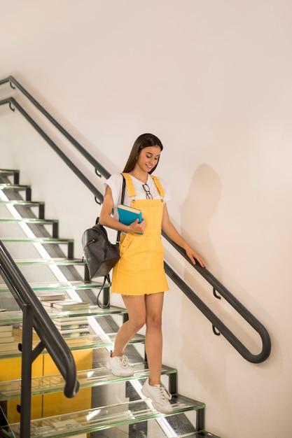 Teen schoolgirl walking downstairs with book Free Photo