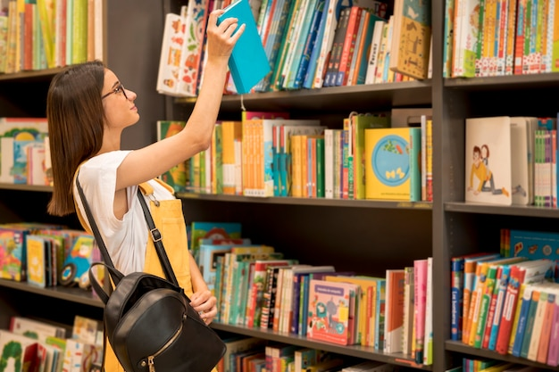 Teen schoolgirl with backpack picking book from shelf Free Photo