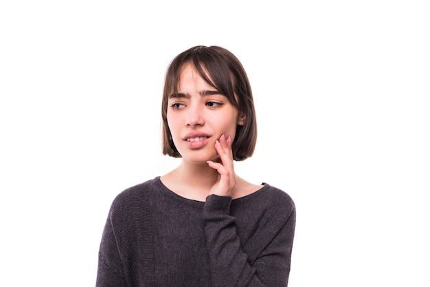Teen woman pressing her bruised cheek with a painful expression as if she's having a terrible tooth ache. Free Photo