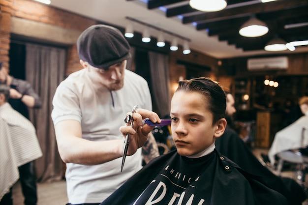 Teenage boy haircuts hairdresser in the barber shop. fashionable stylish retro hairstyle Premium Photo