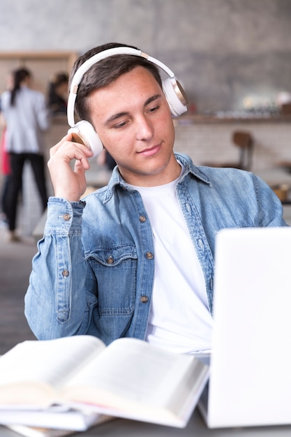 Teenage boy in headphones sitting at table in classroom Free Photo