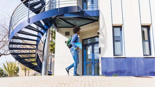 Teenage boy holding book in hand walking in front of university building Free Photo