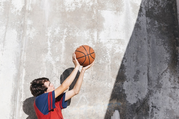 Teenage boy practicing basketball in front of wall Free Photo