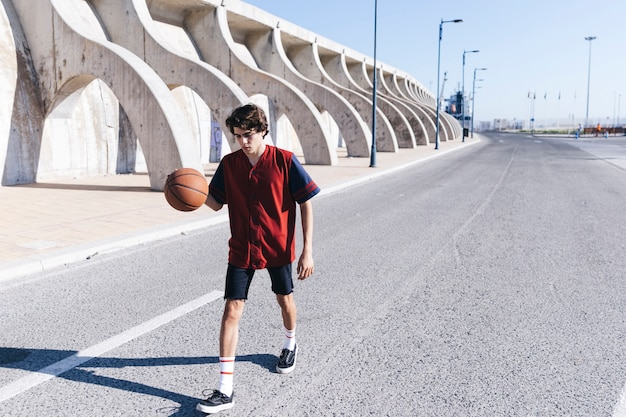 Teenage boy practicing basketball on road Free Photo