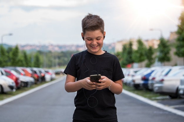 Teenage boy smiling while texting his friends via social networks using mobile phone, sitting against urban landscape Premium Photo