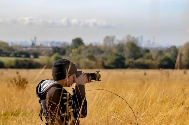 自然保護区でデジタル一眼レフカメラで写真を撮る10代の少年 Premium写真