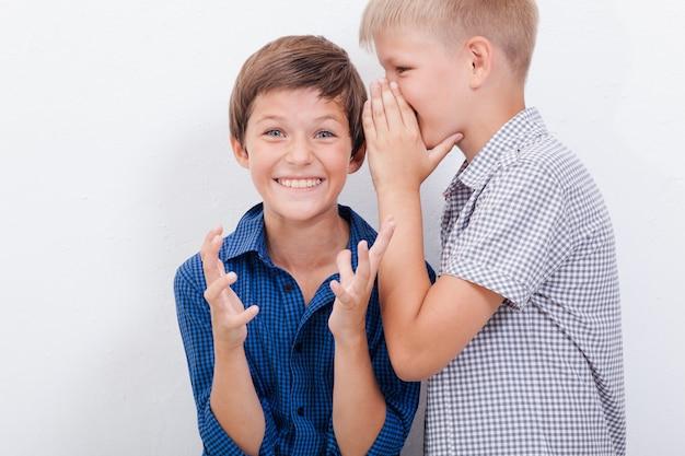 白い背景に驚いた友人の耳に秘密をささやく10代の少年 無料写真