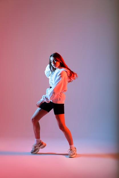 Подростковая женщина танцует хип-хоп в студии, повседневная одежда Premium Фотографии