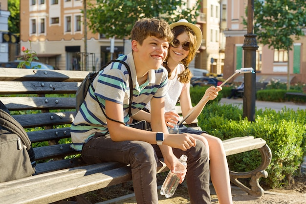 Teenage friends girl and boy sitting on bench in city, smiling, talking Premium Photo
