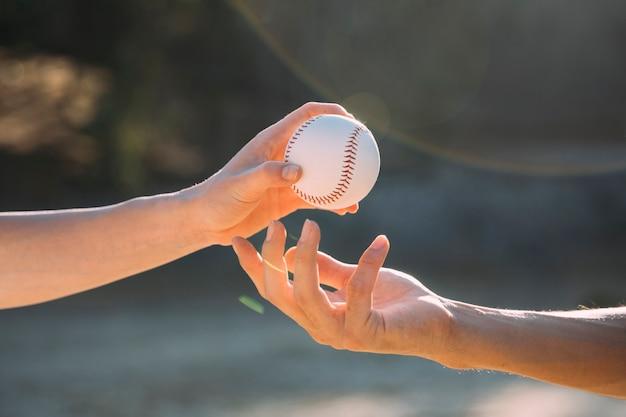 Teenage friends passing baseball Free Photo