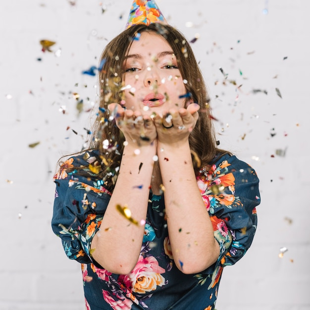 Teenage girl blowing confetti from hand against white backdrop Free Photo
