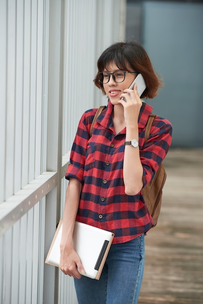 Teenage girl in casualwear calling a friend while walking from school Free Photo