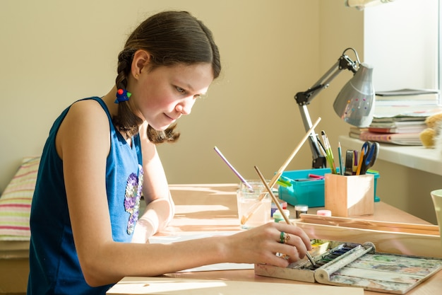 Teenage girl draws watercolor at a table in room Premium Photo