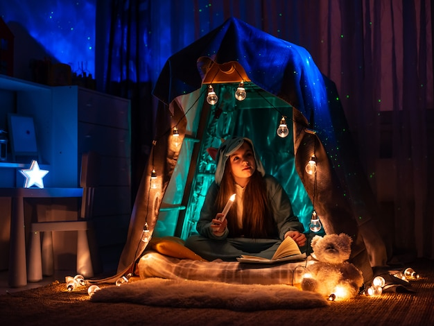 Teenage girl in the form of anime sitting in the game home tent. scenery with fantastic garland lighting Premium Photo
