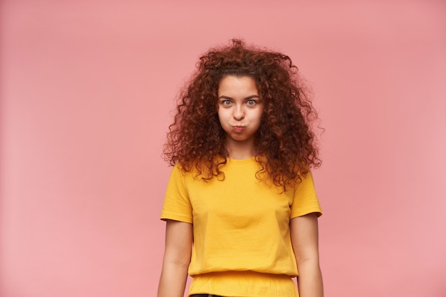 Teenage girl, funny looking woman with ginger curly hair wearing yellow t-shirt Free Photo