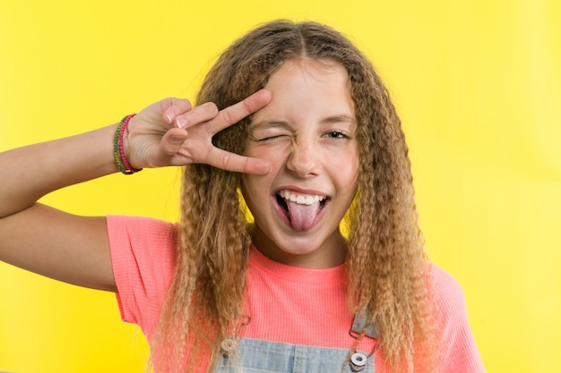 Teenage girl gesticulating, showing tongue, covering one eye Premium Photo
