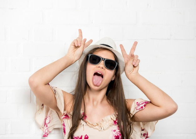 Teenage girl grimacing sticking out tongue and showing two fingers Free Photo