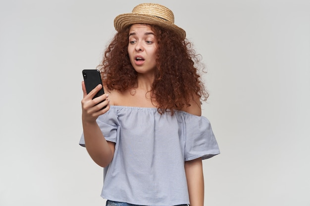 Teenage girl, happy looking woman with curly ginger hair. wearing striped off-shoulders blouse and hat. holding and watching at her smartphone, unhappy face. stand isolated over white wall Free Photo