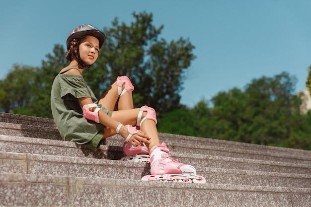 Ragazza adolescente in un casco impara a guidare sui pattini a rotelle tenendo un equilibrio o sui rollerblade e girare per la strada della città nella soleggiata giornata estiva Foto Gratuite