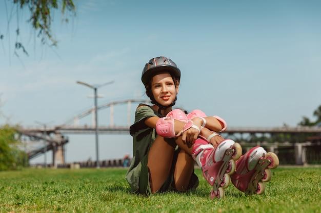 L'adolescente in un casco impara a cavalcare sui pattini a rotelle all'aperto Foto Gratuite