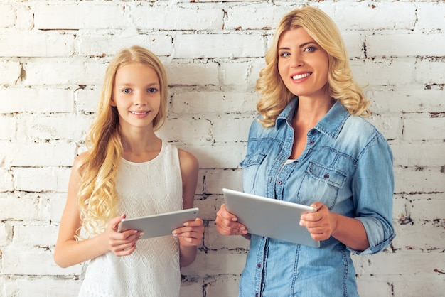 Teenage girl and her mother are holding tablets. Premium Photo