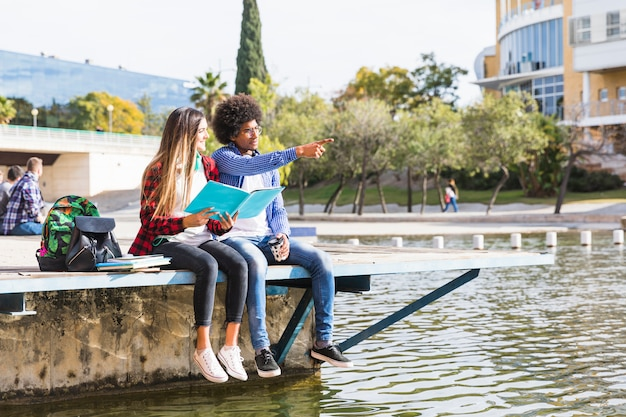 Teenage girl holding book in hand looking at his boyfriend showing something near the lake Free Photo