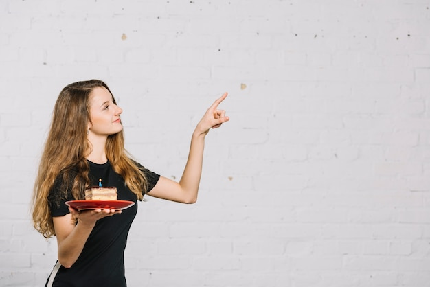 Teenage girl holding slice of cake with candle pointing her finger at something Free Photo