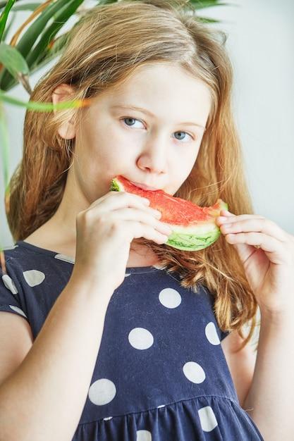 スイカを食べる水玉模様の青いドレスを着た10代の少女。 Premium写真