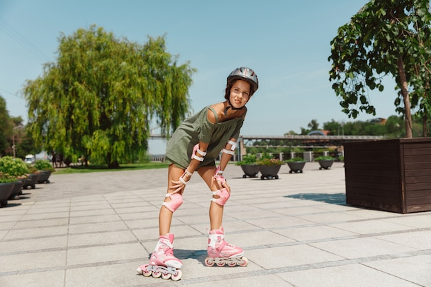 ヘルメットをかぶった10代の少女は、晴れた夏の日に、バランスをとったりローラーブレードをしたりして、街の通りでスピンするローラースケートに乗ることを学びます。健康的なライフスタイル、子供時代、趣味、レジャー活動。 無料写真