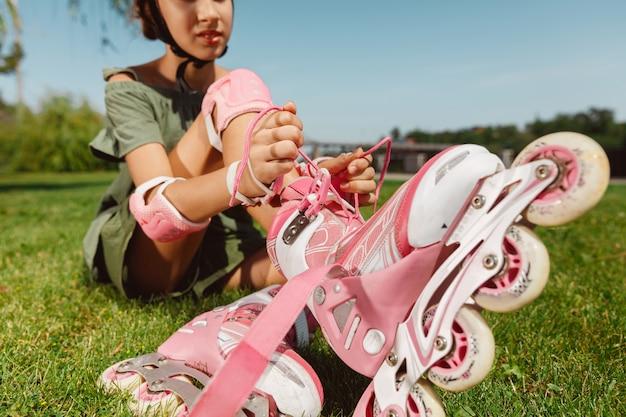 ヘルメットをかぶった10代の少女は、晴れた夏の日に、バランスまたはローラーブレードを持ってローラースケートに乗って街の通りでスピンすることを学びます 無料写真