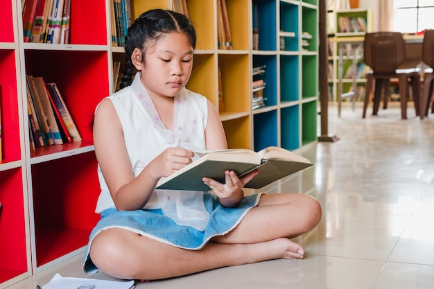 Teenage girl reading book in library.education and literacy concept Premium Photo