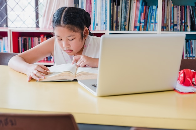 Teenage girl reading book with laptop computer in library.education and literacy concept Premium Photo