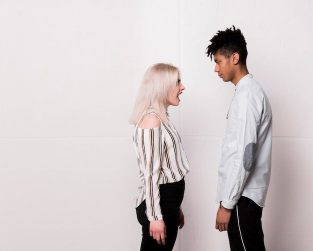 Teenage girl screaming on her boyfriend seriously looking at him against white floor Free Photo